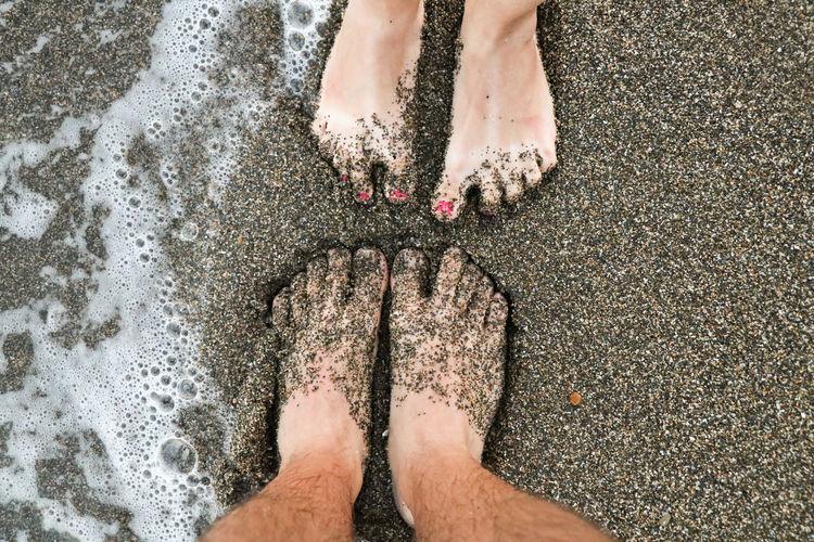 Low section of woman standing on wet sand