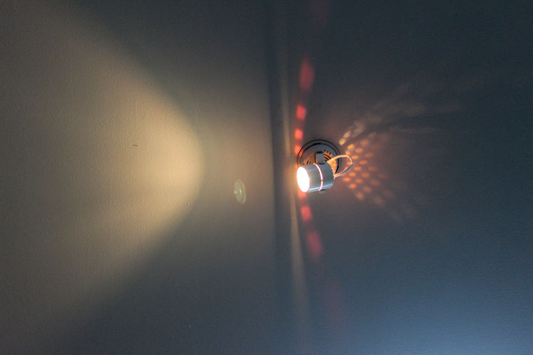 Low angle view of illuminated light bulb hanging from ceiling