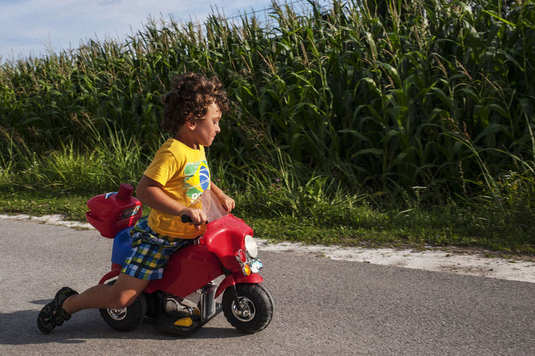Side view of boy riding motorcycle