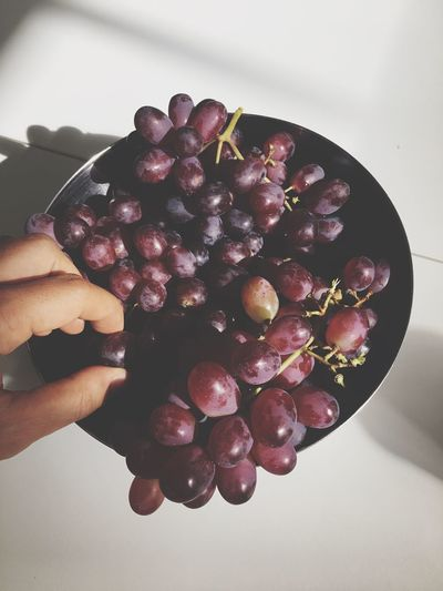 Cropped Hand Plucking Red Grape From Bunch In Bowl On Table