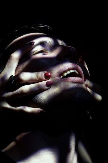 Close-up portrait of woman with hand on black background