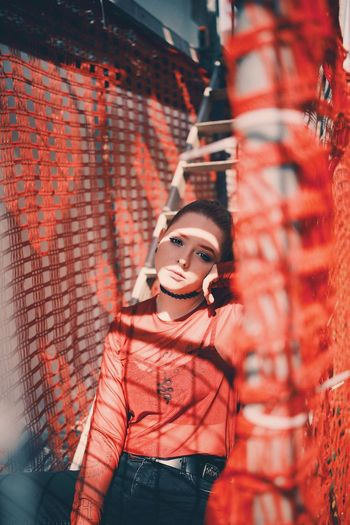 Portrait of young woman sitting on ladder amidst red net