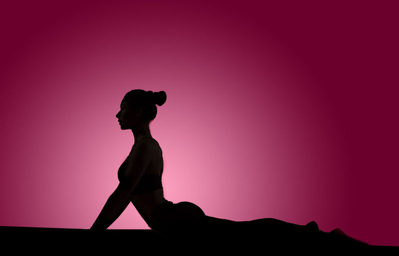 Silhouette woman doing yoga on pink background