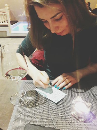 High Angle View Of Woman Writing On Paper While Sitting At Table
