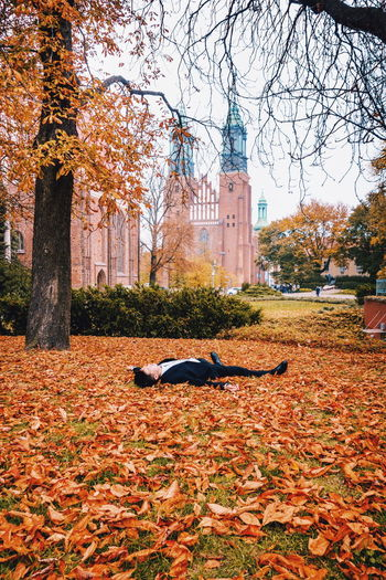 Young woman lying down in park during autumn