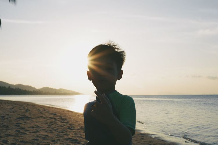 Boy standing on beach against sky during sunset