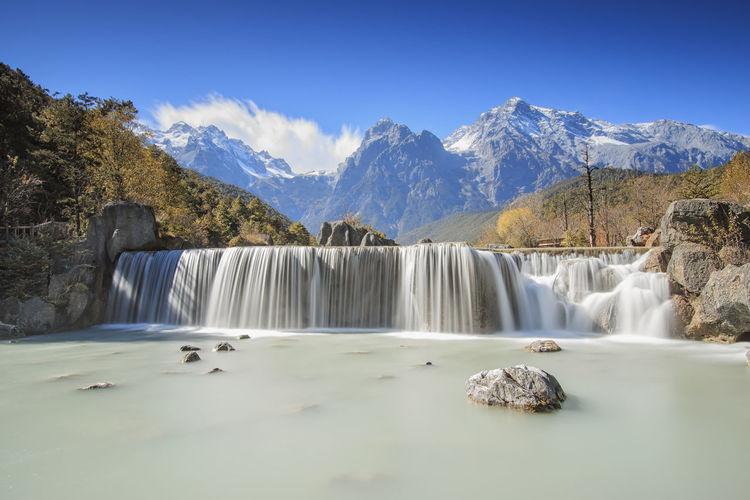 Idyllic waterfall with jade dragon snow mountain in background