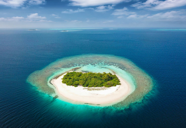 Small, uninhabited island in the tropical sea of the Maldives Green Palm Tree Above Aerial Beach Beauty In Nature Blue Day Horizon Over Water Island Nature No People Outdoors Paradise Reef Round Sand Scenics Sea Sky Tranquil Scene Tranquility Uninhabited Water