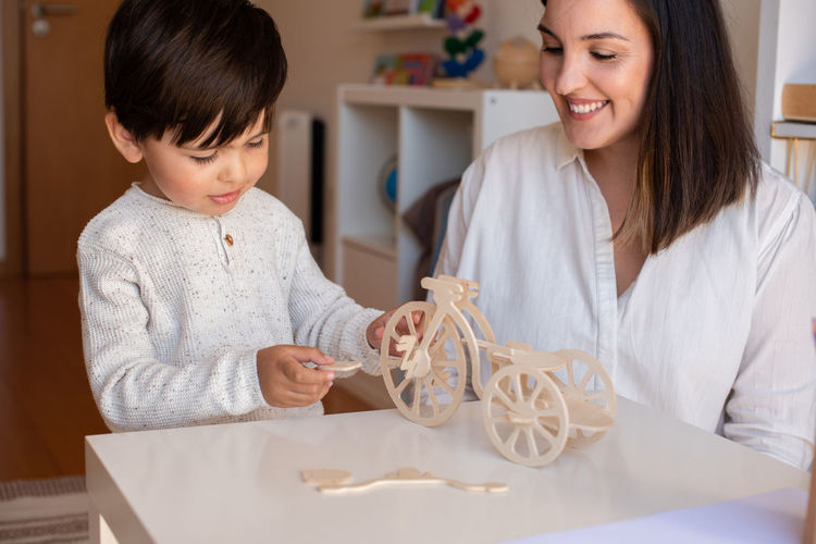 Happy woman holding baby while sitting on table