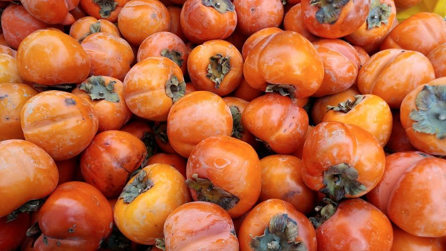 EyeEm Selects a pile of fuyu persimmons. Fuyu Persimmons Organic Produce Farmers Market California Hero Image Healthy Lifestyle Fruit Autumn Colors Backgrounds Orange Color Chinese Fruit