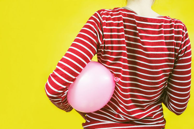 One Person Striped Colored Background Midsection Studio Shot Yellow Indoors  Red Standing Adult Women Casual Clothing Front View Human Body Part Balloon Yellow Background Lifestyles Holding Fashion Top - Garment Childhood Children Back Party Time Composition Color Vibrant Color Vibrant Contrast Red