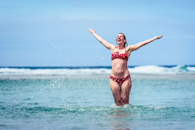 Happy mid adult woman with arms outstretched in sea against sky