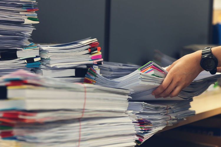 Cropped hands of businesswoman holding files on desk in office