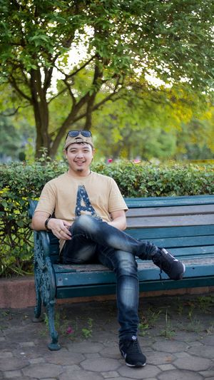 Portrait of smiling man sitting on bench in park