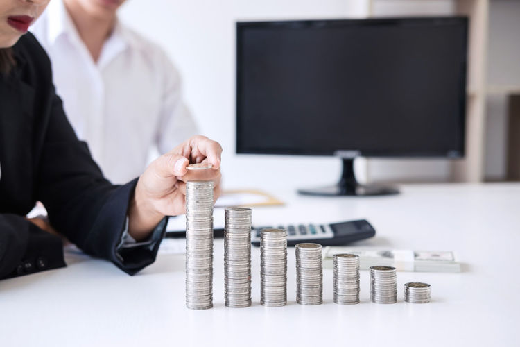 Businessman stacking coins on table