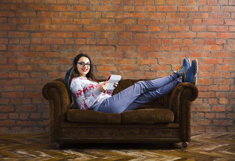 Full length of woman sitting on sofa against brick wall