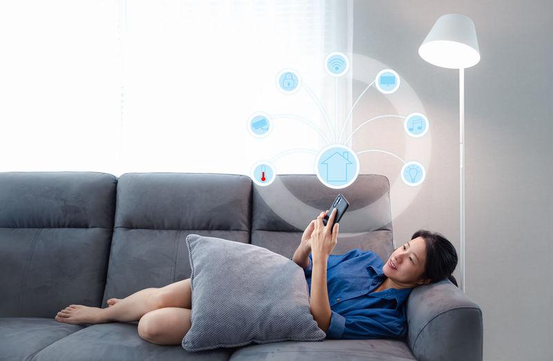Young woman using mobile phone on sofa