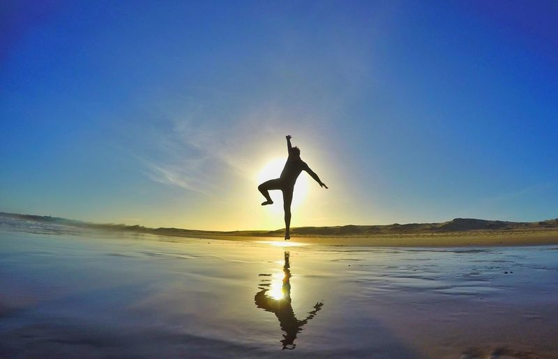 Silhouette of man jumping at beach against sky during sunset