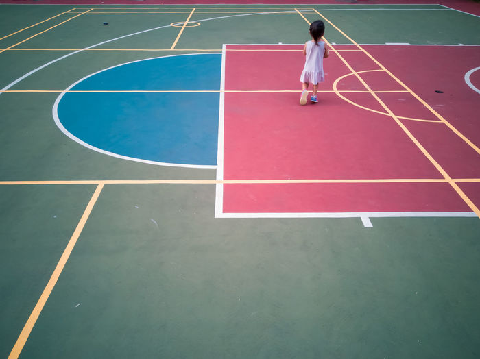 Full length of girl playing with basketball
