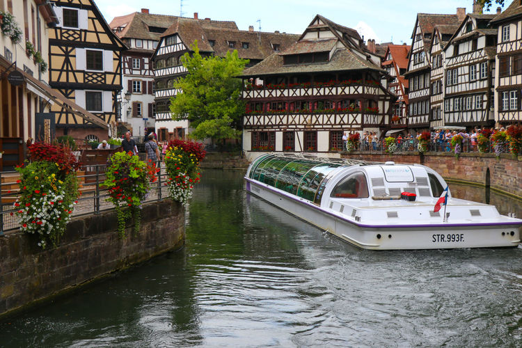 Canal in Strasbourg Water Nautical Vessel Transportation Mode Of Transportation Architecture Built Structure Building Exterior Waterfront River Building Day Nature City Incidental People Craft Passenger Craft Plant Outdoors Canal