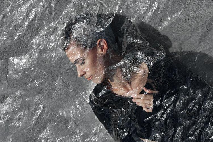 Woman seen through plastic against wall