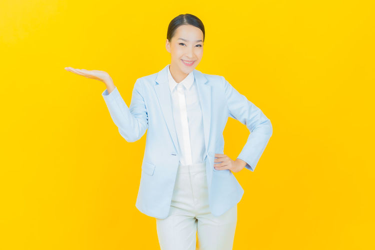 Portrait of a smiling young woman over yellow background