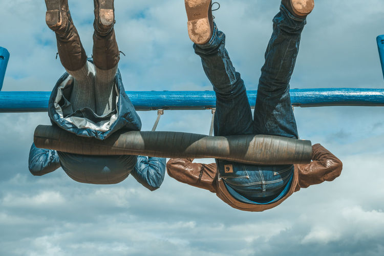 Low section of people swinging against sky