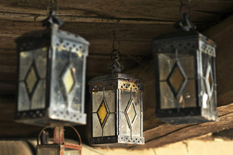 Low Angle View Of Vintage Lanterns Hanging In Old Mud House