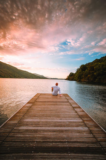Man on pier over lake against sky during sunset