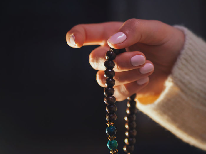 Cropped hand holding rosary beads