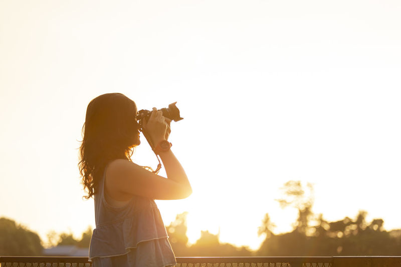 Side view of woman photographing against sky during sunset