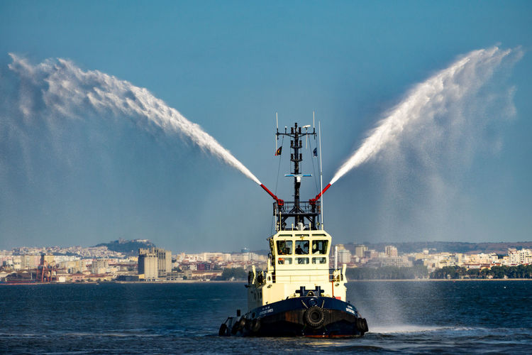 Tugboat on River Tagus, Lisbon, Portugal, using its water jets. EyeEm Selects Portugal Architecture Building Exterior Built Structure City Cloud - Sky Day Ferry Lisbon Mode Of Transport Motion Nature Nautical Vessel No People Outdoors Sea Sky Tagus River Transportation Travel Destinations Tugboat Vapor Trail Water Waterfront