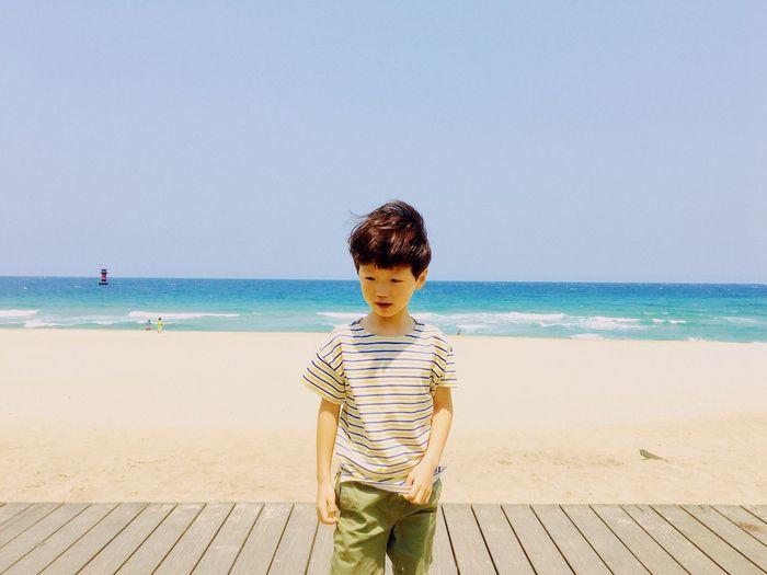 Boy standing on beach against clear sky