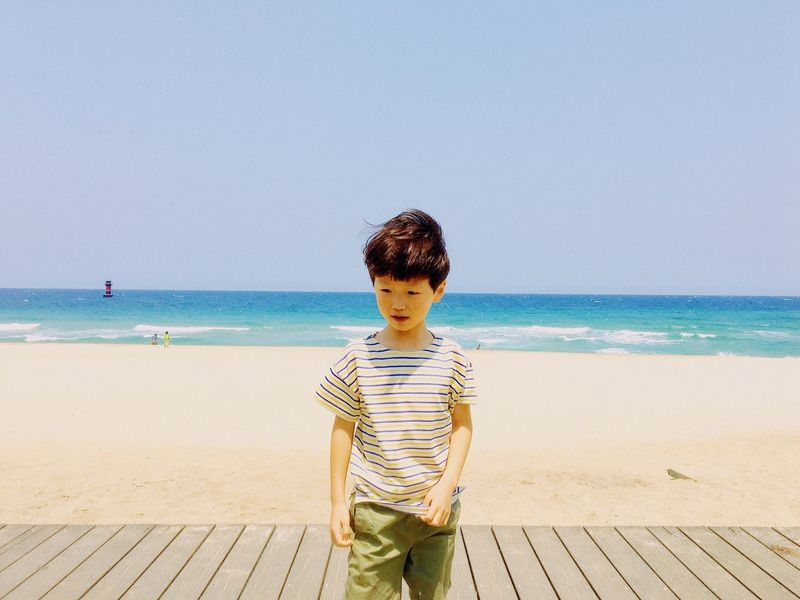 EyeEm Selects Sea Boys Beach Horizon Over Water One Person Real People Leisure Activity Childhood Casual Clothing Standing Water Three Quarter Length Sand Nature Outdoors Day Elementary Age Front View Beauty In Nature Clear Sky