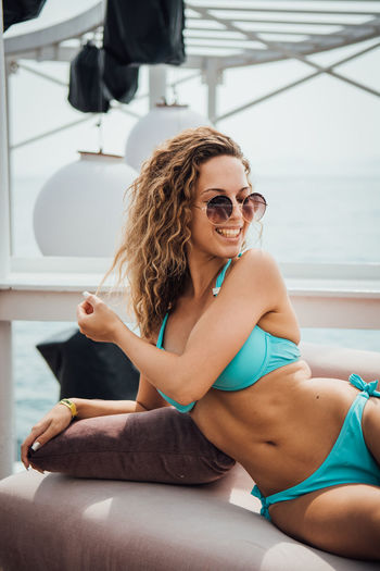 Young woman wearing sunglasses relaxing on sofa
