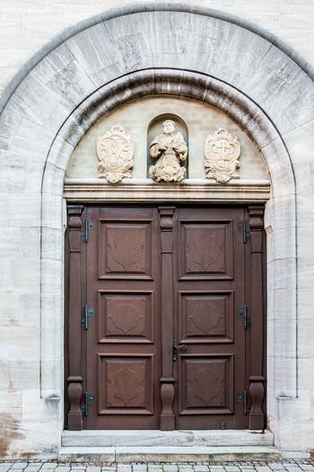 Old door of a historical building with statues and coats of arms made of stone Entrance Door Architecture Closed Built Structure Building Exterior No People Safety Representation Security Protection Art And Craft Day Human Representation Arch Building Male Likeness Craft Creativity Wood - Material Outdoors Wood Bas Relief Ornate