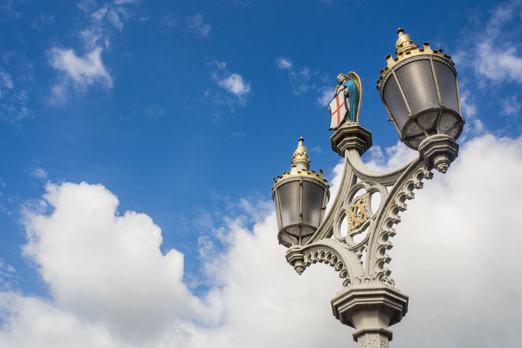 Low angle view of statue of street light against cloudy sky