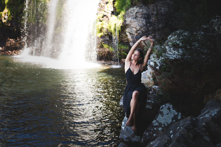 Woman sitting on rock by waterfall in forest
