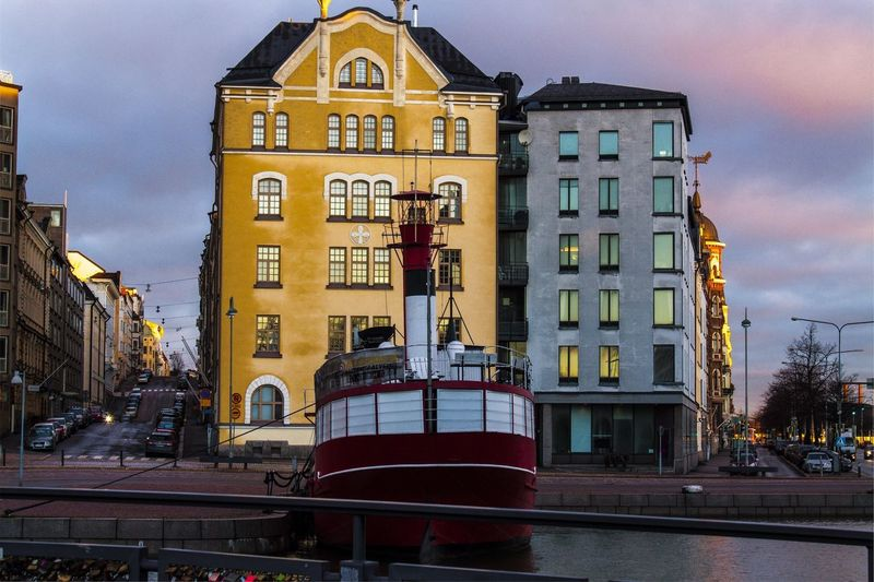 Boat Moored At Harbor Against Buildings In City