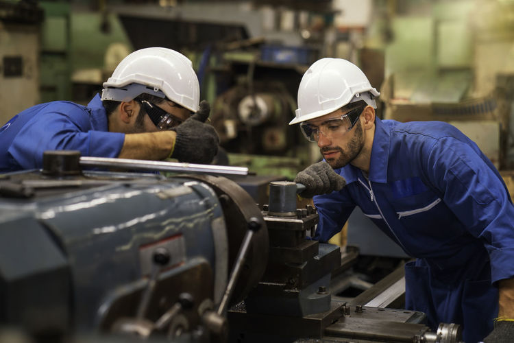 Engineers working together over machinery at factory