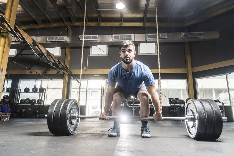 Man looking away while picking barbell at gym