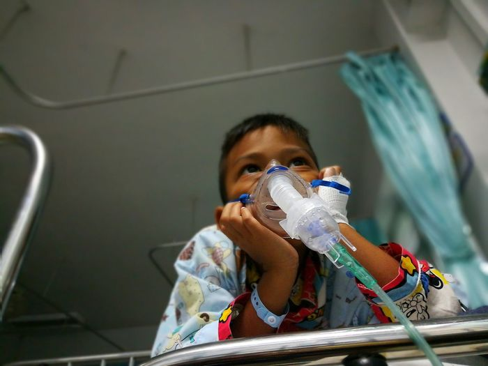 Low Angle View Of Boy With Oxygen Mask In Hospital