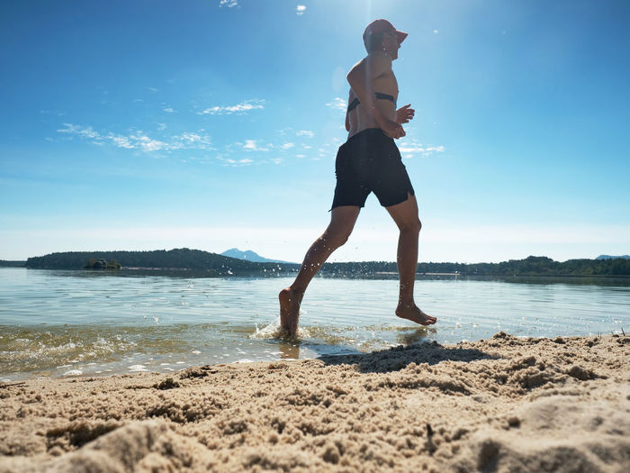 Runner run in water at beach, water drops refreshing his body. training with heart rate monitor