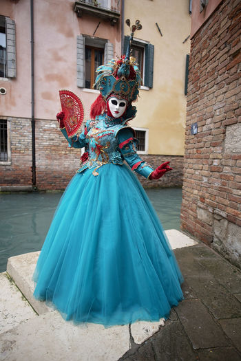 Portrait of woman in carnival costume standing by canal in city