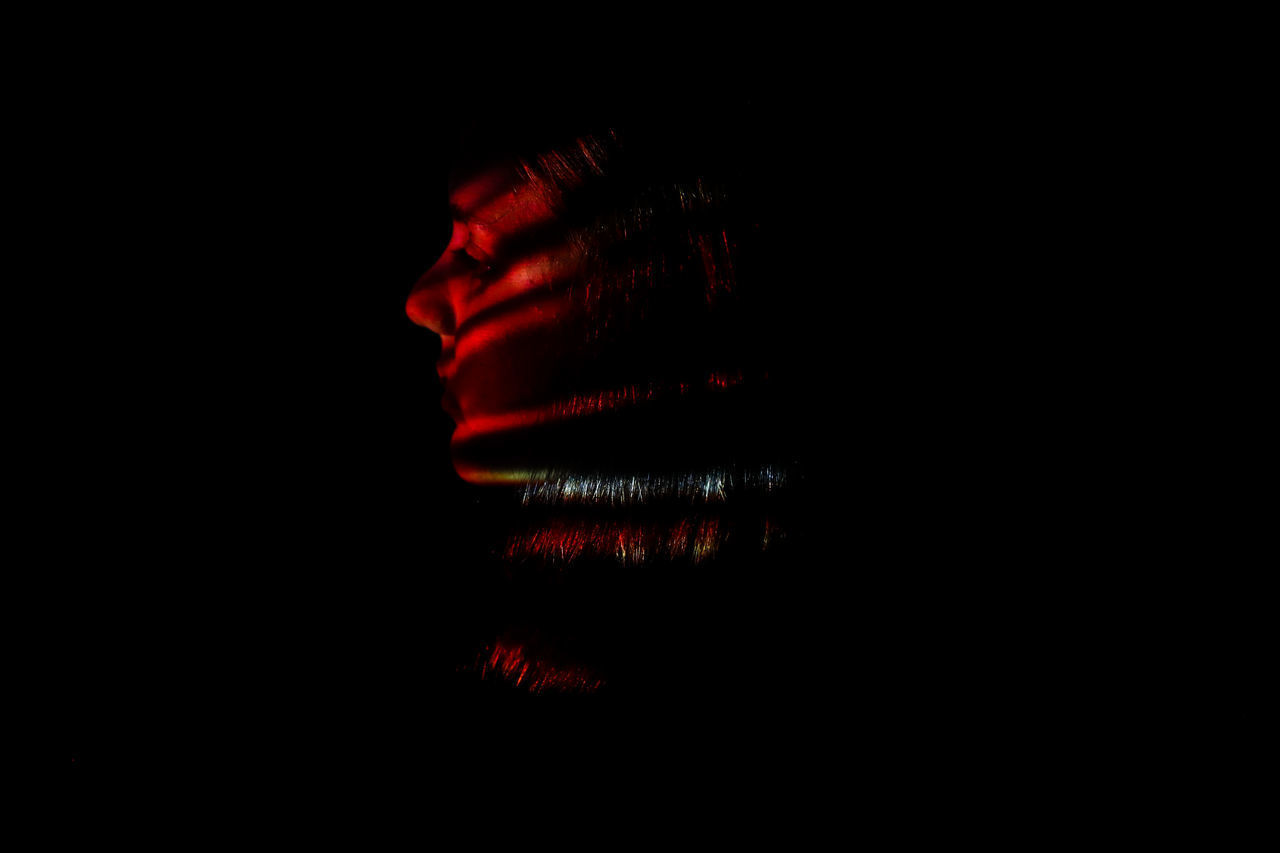studio shot, red, indoors, copy space, black background, one person, close-up, human body part, body part, dark, domestic room, illuminated, human hair, unrecognizable person, cut out, women, human face, depression - sadness, human limb
