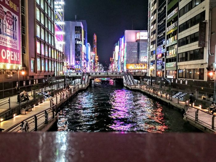 Canal amidst buildings at dotonbori during night
