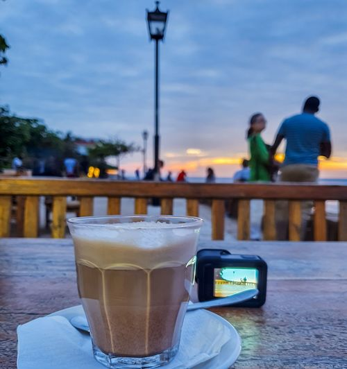 People in coffee cup on table at cafe against sky