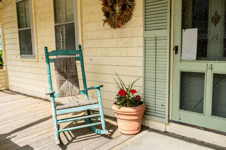 Rocking chair with potted plant at porch of house