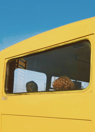 View of people sitting in bus seen through window