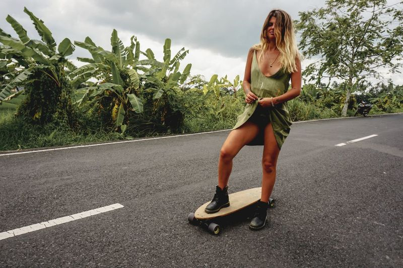 Young Woman On Skateboard Against Sky